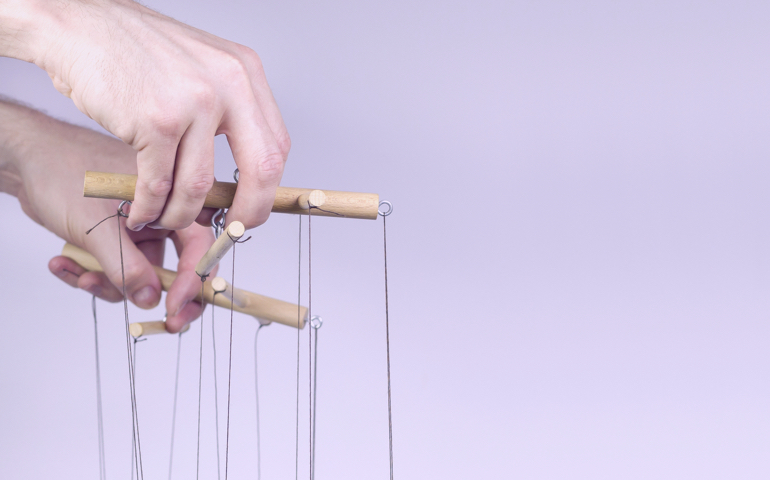 Hand holding the strings of a puppet.