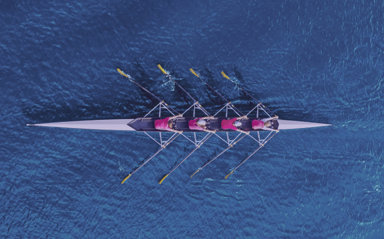 A team on a river, rowing.
